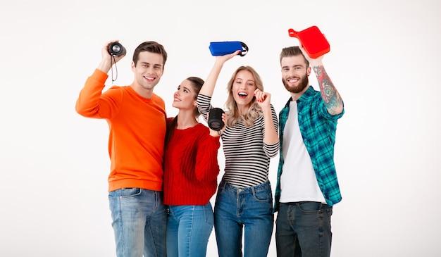 Empresa jovem hippie de amigos se divertindo juntos, sorrindo, ouvindo música em alto-falantes sem fio