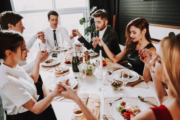 Empresa jovem senta-se em ternos ao redor da mesa de jantar