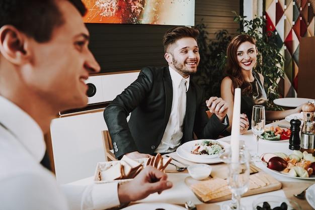 Empresa jovem senta-se em ternos ao redor da mesa de jantar.