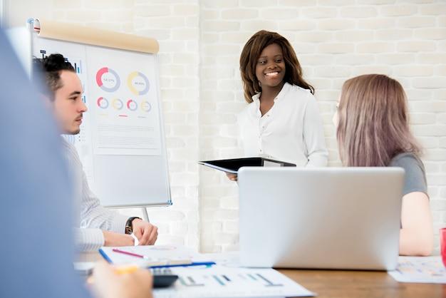 Empresária africana com seus colegas multiétnicas na apresentação da reunião de vendas