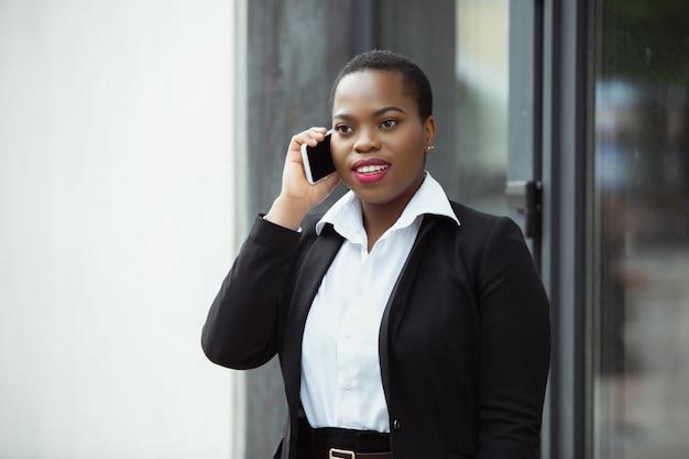 Empresária afro-americana em traje de escritório sorrindo, parece confiante e feliz, ocupado
