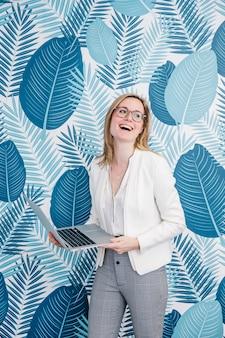 Empresária alegre em pé com laptop