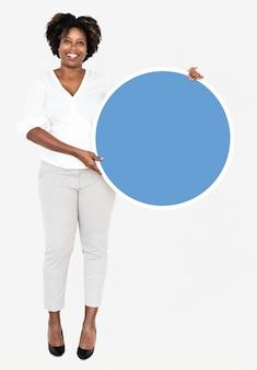 Empresária alegre segurando uma placa redonda azul