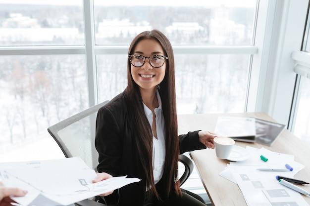Empresária alegre tomando café e trabalhando com documentos no escritório