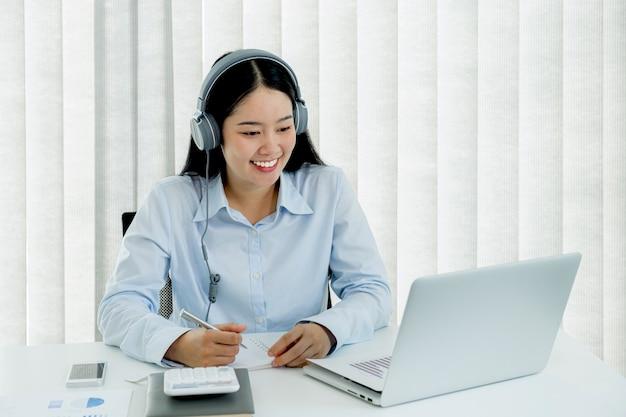Empresária analisa o gráfico e realiza videoconferência com laptop no escritório em casa