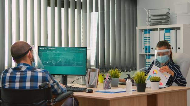 Empresária analisando estatísticas financeiras, conversando com um colega de trabalho deficiente sentado em uma cadeira de rodas, trabalhando no novo escritório normal de negócios, usando proteção facial contra covid-19.