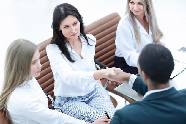 Empresária apertando a mão do parceiro em reunião de escritório