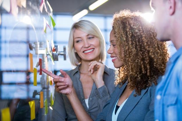 Empresária, apontando na nota pegajosa enquanto explica colegas