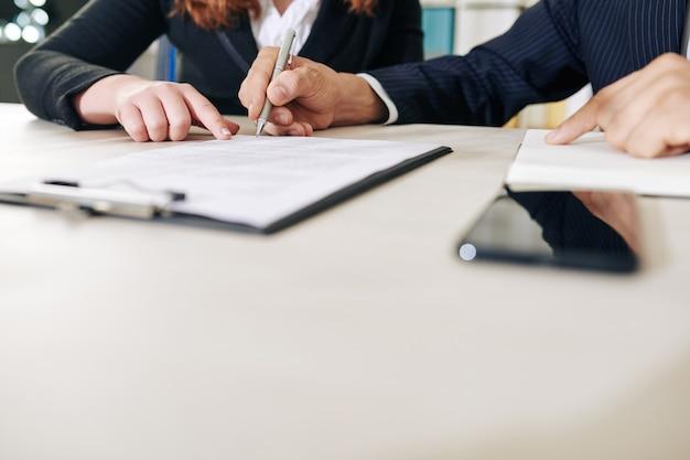 Empresária apontando para um documento financeiro ao pedir a um colega para cantá-lo