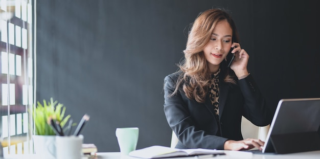 Empresária asiática atraente, falando ao telefone com o cliente