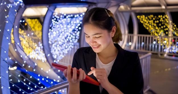 Empresária asiática bonita verificando o trabalho via tablet via internet no caminho