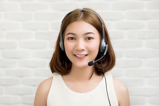 Empresária asiática casual usando fone de ouvido microfone como agente de atendimento ao cliente de telemarketing