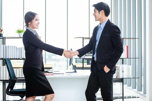Empresária asiática e empresário apertando as mãos na sala de escritório