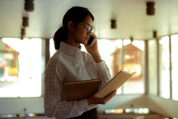 Empresária asiática ocupada usando smartphone falando sobre discussão de negócios durante a leitura de relatório financeiro
