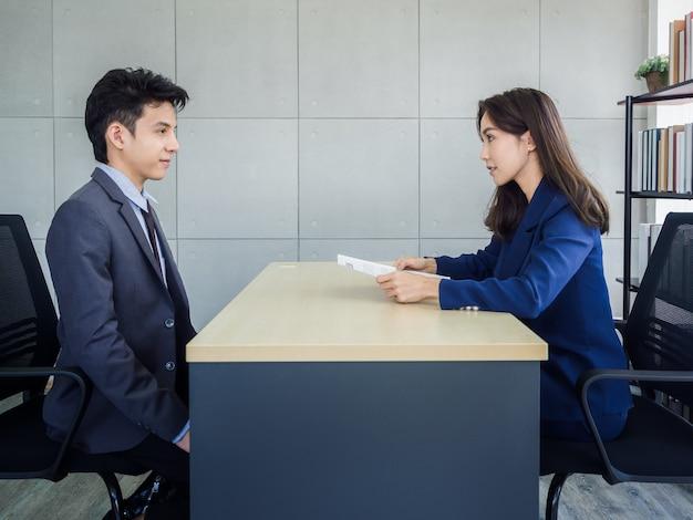 Empresária asiática, rh analisa currículo de jovem empresário asiático de terno no cargo
