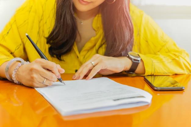 Empresária assinar contrato documento papel na mesa de madeira.