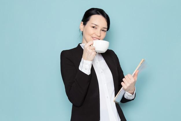 Empresária, bebendo café e segurando a revista