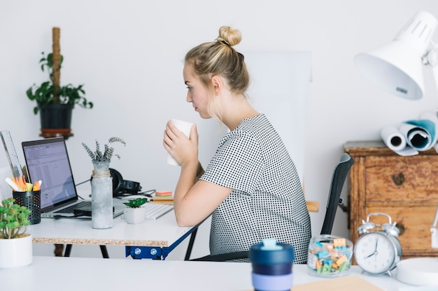 Empresária beber café enquanto trabalhava no escritório