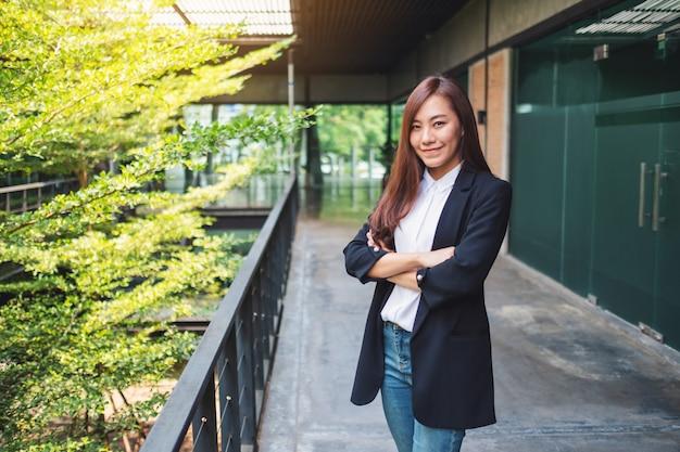 Empresária bem sucedida asiática em pé no escritório
