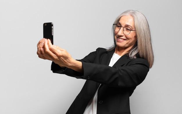 Empresária bonita sênior com um telefone inteligente.