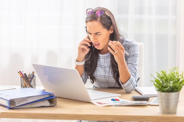 Empresária chateada, gritando para o celular gesticulando, enquanto está sentada na frente de seu computador no escritório.