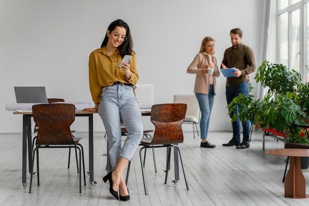 Empresária checando seu telefone enquanto seus colegas de equipe conversam