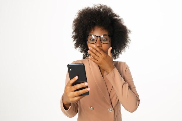 Empresária chocada usando óculos e celular