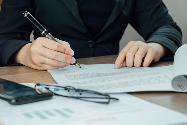 Empresária close-up, assinando os termos e o documento de acordo em sua mesa
