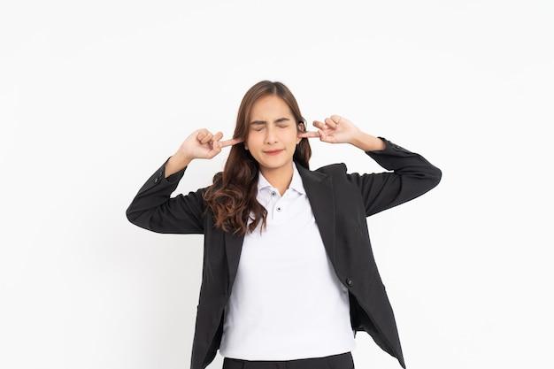 Empresária cobrindo as orelhas com os dedos e fechando os olhos