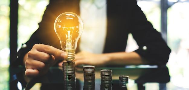 Empresária, colocando a lâmpada sobre a pilha de moedas na mesa para economizar energia e dinheiro conceito