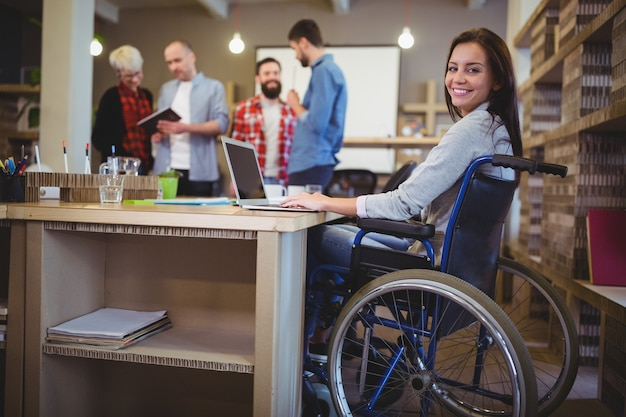 Empresária com deficiência confiante usando laptop no escritório