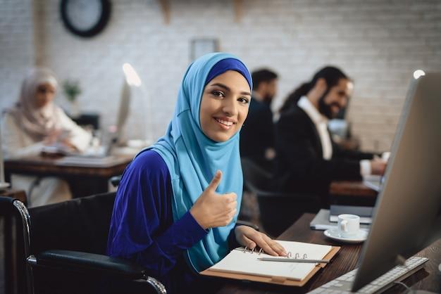 Empresária com deficiência em hijab, mostrando o polegar