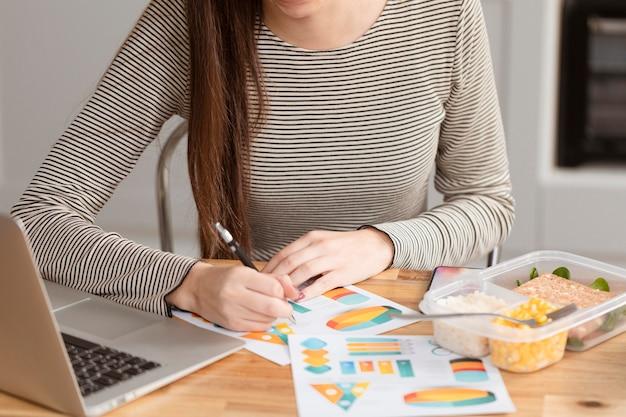 Empresária com fome comendo e escrevendo