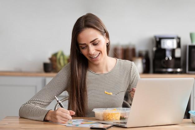 Empresária com fome comendo e lição de casa