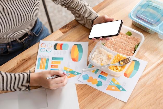 Empresária com fome comendo e olhando para gráficos