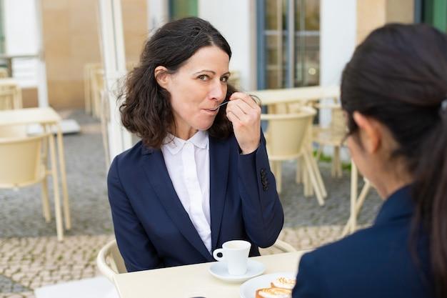 Empresária comendo sobremesa e olhando