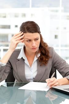Empresária concentrada tomando notas enquanto trabalha no laptop dela