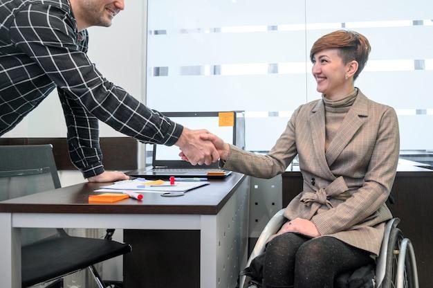 Empresária confiante em cadeira de rodas, apertando as mãos