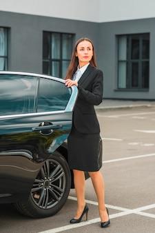 Empresária confiante em pé perto da porta do carro aberta