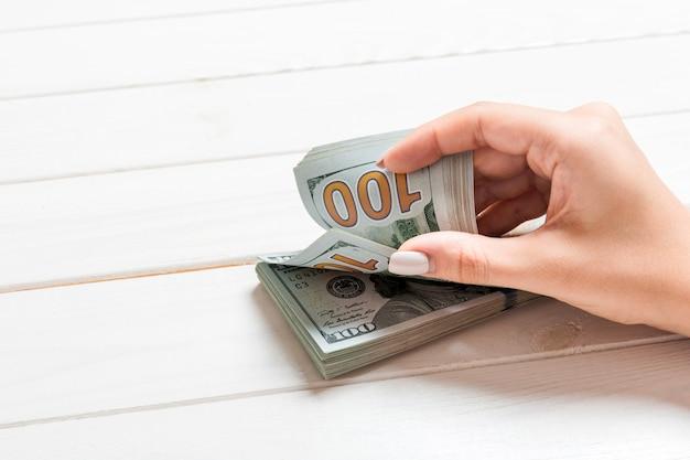 Empresária contando notas de cem dólares em fundo de madeira