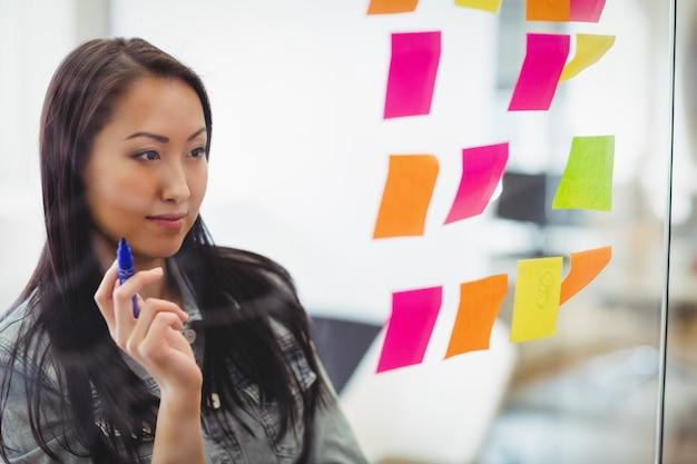 Empresária criativa confiante olhando para notas auto-adesivas coloridas