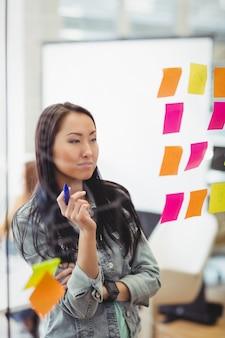 Empresária criativa olhando notas auto-adesivas coloridas