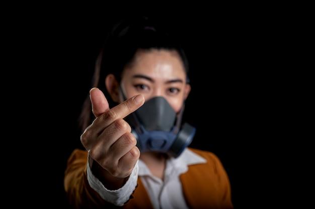 Empresária da jovem mulher asiática que coloca um respirador n95 máscara para proteger das doenças respiratórias transportadas pelo ar as mulheres é sinal de mão mini coração