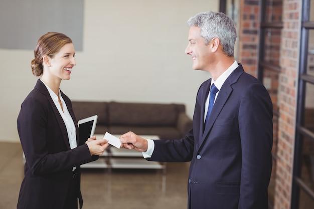 Empresária dando cartão de visita para cliente no escritório