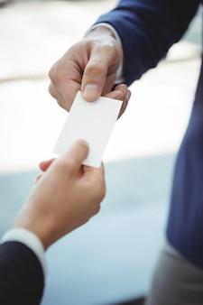 Empresária dando cartão de visita para empresário na plataforma