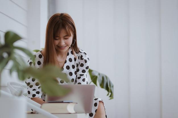 Empresária de ásia, usando o computador portátil, trabalhando com feliz
