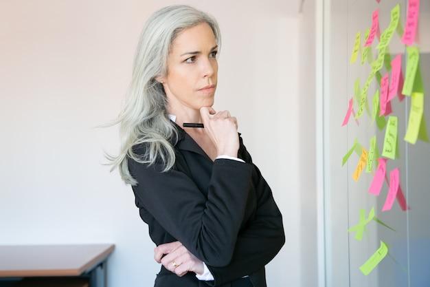 Empresária de cabelos grisalhos pensativa lendo notas na parede de vidro e segurando o marcador. trabalhadora caucasiana concentrada em terno pensando na ideia para o projeto.