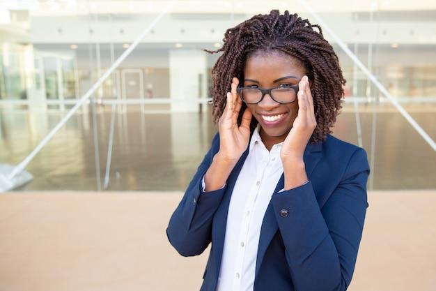 Empresária de conteúdo atraente, ajustando óculos