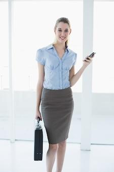 Empresária de conteúdo calmo segurando seu smartphone e maleta
