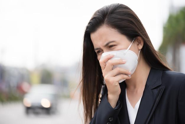 Empresária de fato usando máscara protetora e tosse